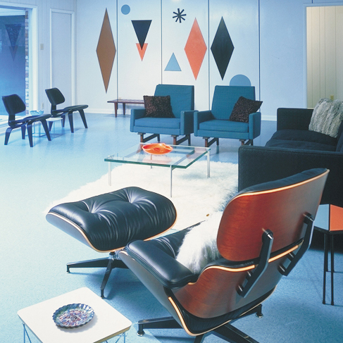 A lounge chair positioned infront of a living room, with a geometry wall mural composed of layers of laminate surfaves.