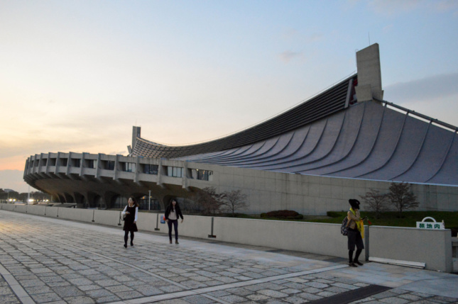 Exterior photo of concrete arena with swooping, wave-like design