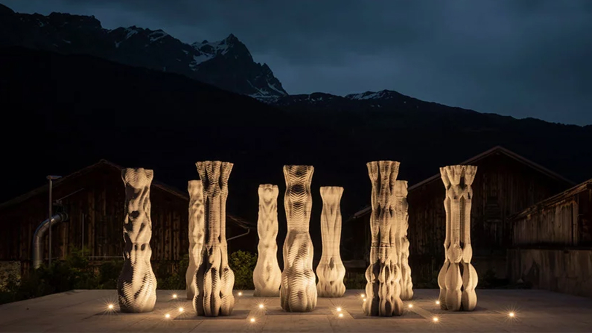 Nine concrete columns are lit below in front of a mountain in a nighttime scene thanks to the team from ETH Zurich