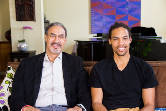 Two African American men seated next to each other, one of whom is Phil Freelon