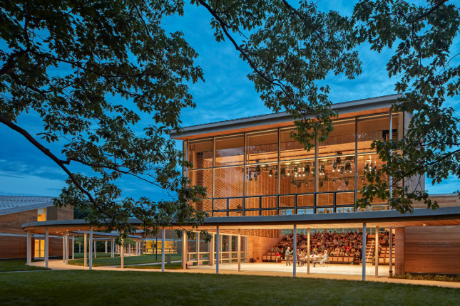 Twilight image of two story structure with performance lighting up interior, and pavilion leading to other structures