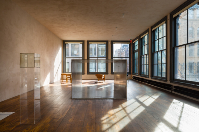 Interior of the Donald Judd Foundation home, a beige room framed by a square coffee table