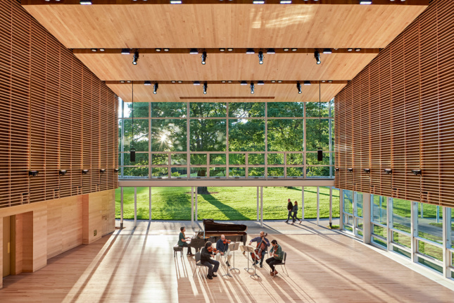 Image of sunlight streaming into wood-clad performance hall with retractable glass walls, Boston Symphony Orchestra quartet performing