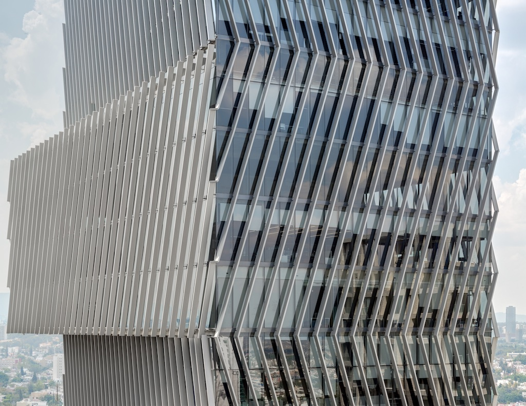 Oversize glass cladding a building with offset volumes and slanted louvers