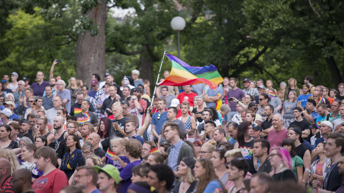 Image of people gathered at vigil, gay pride flag flown in air