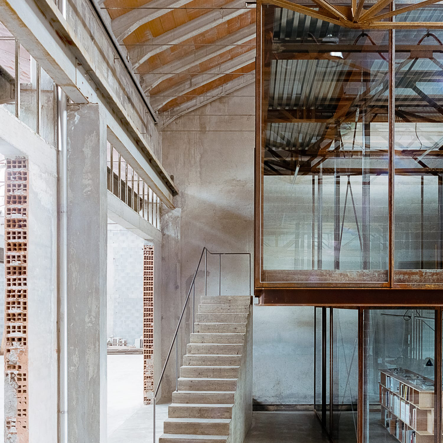 Interior photo of the office of AMAA in Italy, depicting a split between glass and a ruined factory