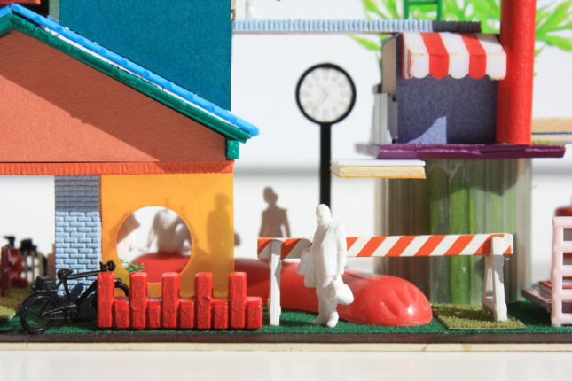 Photo of a model street with a giant hotdog in the background