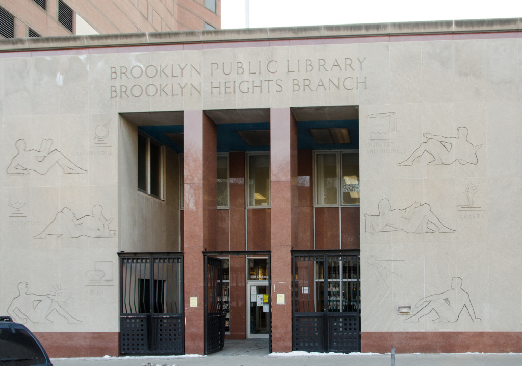 The Brooklyn Heights Library front entrance, featuring reclining people carved into limestone