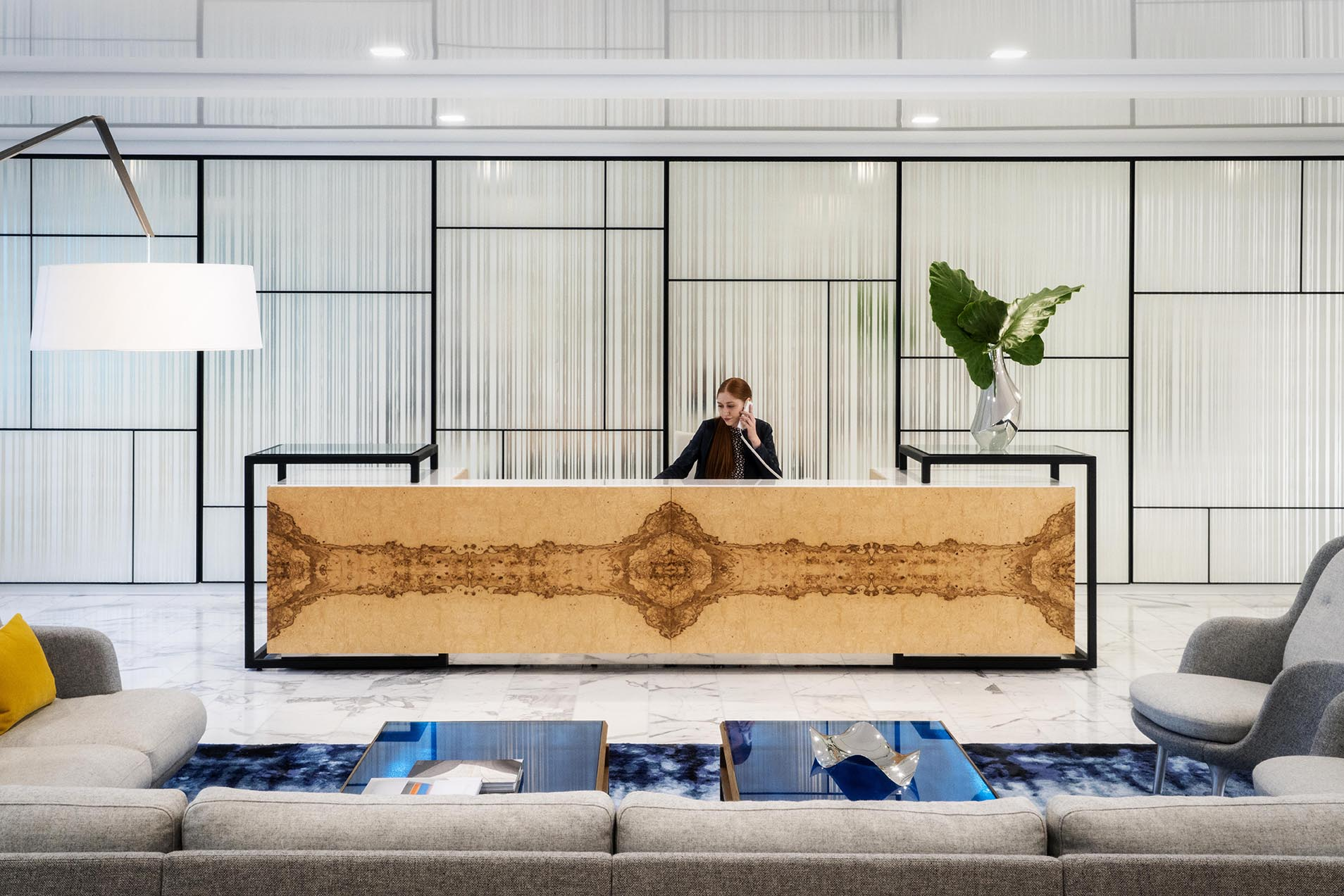 Photo of an office reception area with a wood desk and framed wakk
