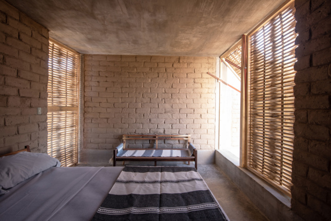 Interior view of bedroom with bench and bamboo lattice windows