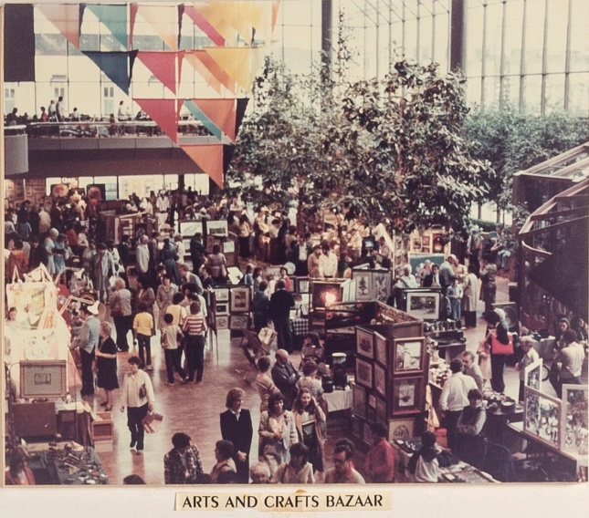 People gathered inside of a mall for a crafts fair