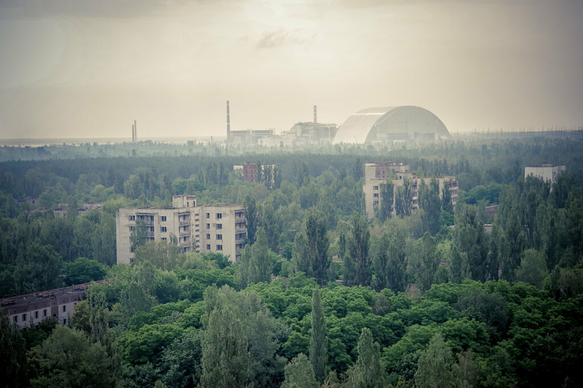 Image of treescape looking on to old nuclear plant, Chernobyl