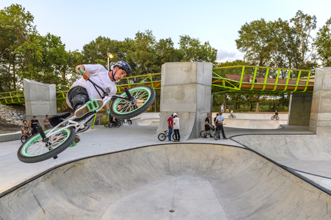 Photo of biker jumping in air off of concrete bowl
