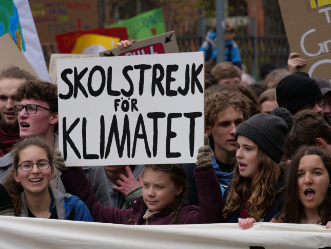 Greta Thunberg holding a sign advocating for climate action, in anticipation of the Global Climate Strike