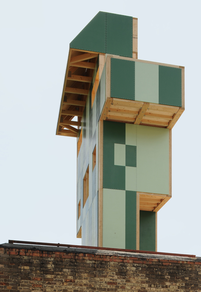 A tall timber pavilion clad in green panels