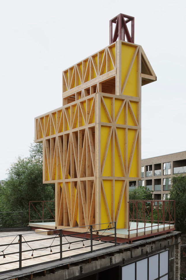 The reverse of a timber pavilion with yellow panels