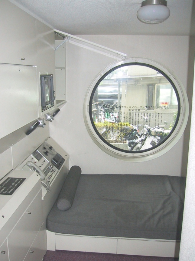 Interior view of a tiny room with porthole