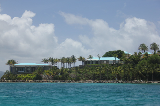 Two low slung buildings on a palm tree island above blue waters, where Jeffery Epstein vacationed