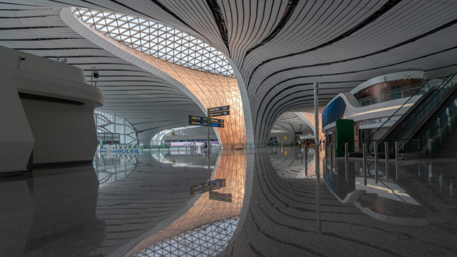 Interior photo of airport with sleek white floor and large skylight above curving walls next to check-in, the Beijing Daxing International Airport