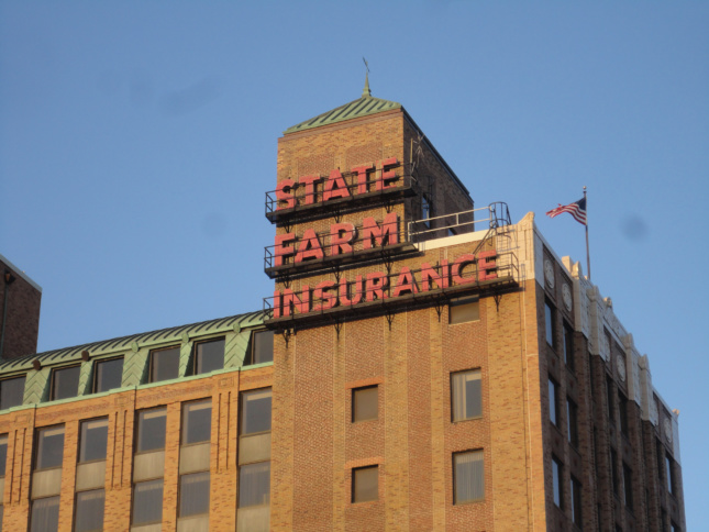 State Farm Insurange in bright red caps on top of a brown masonry building.