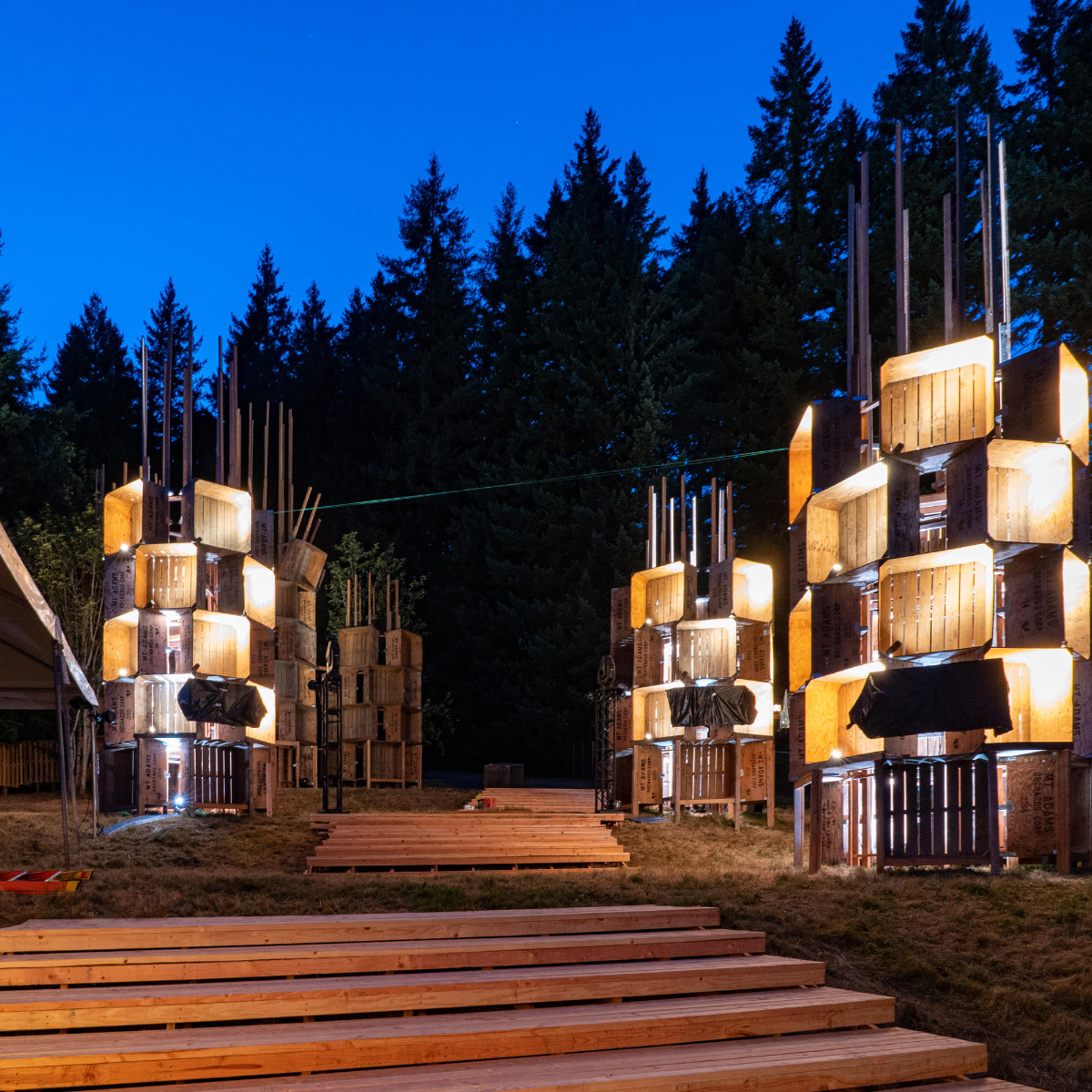 Photo of towers at night made from wooden apple bins, on the PSU campus for the Pickathon Music Festival