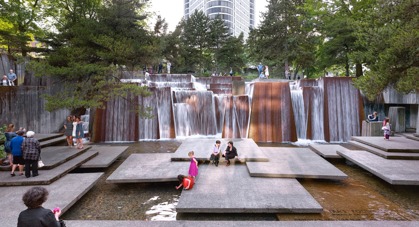 Image of children playing in large urban fountain with square landings and waterfall, from The Cultural Landscape Foundation