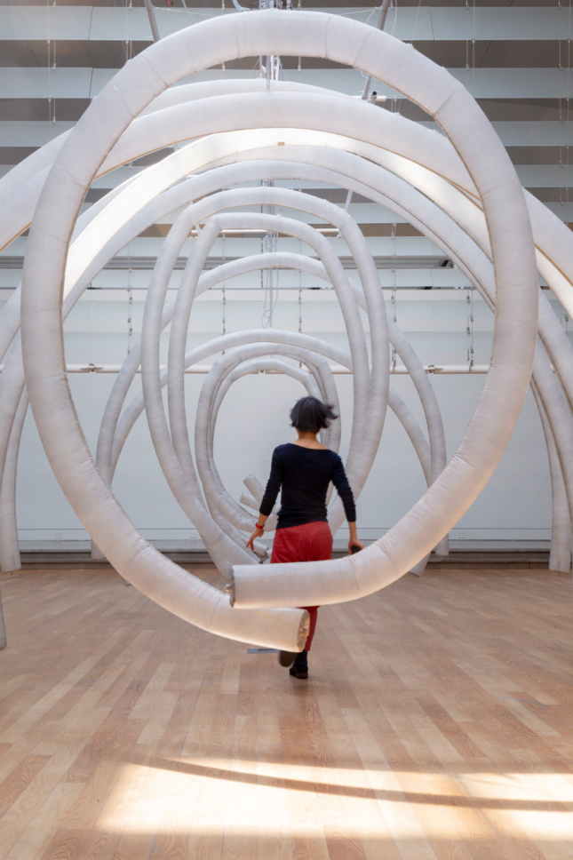 Photo of the Queens Museum atrium with inflatable ribs suspended from the ceiling, with a woman running through the tubes