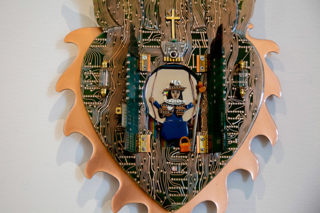 A heart with a saint in the center made from circuit boards