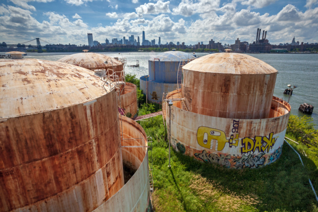 Rusty white oil tanks on a lawn next to a river in Bushwick Inlet Park