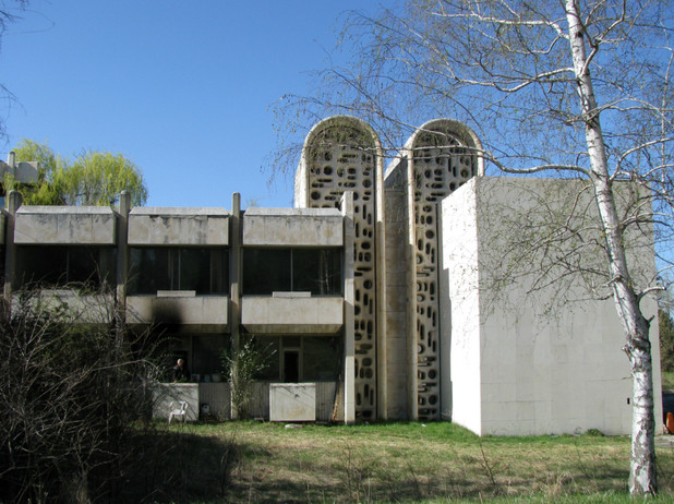 A concrete house with two silos in the center