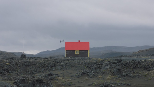 Photo of a house with red roof in an empty landscape