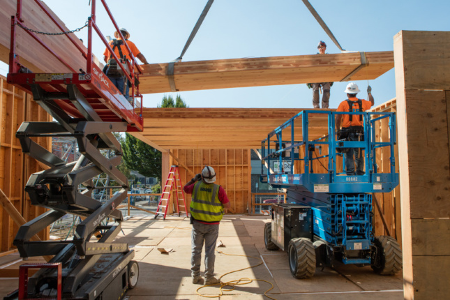 Photo of a wood floorplate being lifted into place