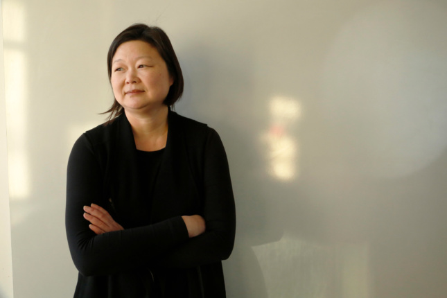 Photo of an Asian woman against a neutral beige background