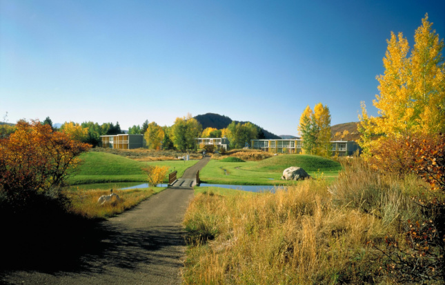 Photo of rolling hills in the summer, with the boxy buildings of the Aspen Institute