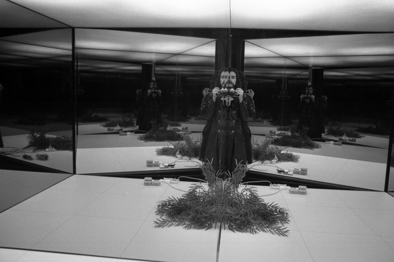 A black and white photo of a man, Cristiano Toraldo di Francia, in a mirrored room