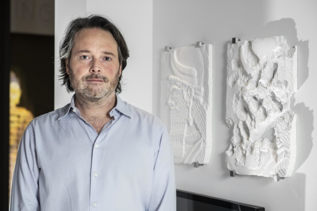 """Artist Piers Secunda with two of his paintings for """"What Remains"""" at the Imperial War Museum London"""