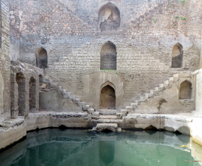 Photo of a stepwell, with staircases descending to a pool of water, taken for the India's Subterranean Stepwells show