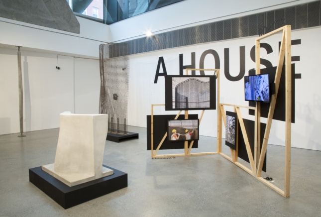 "Timber frame against the words ""A House,"" part of a digital fabrication show"