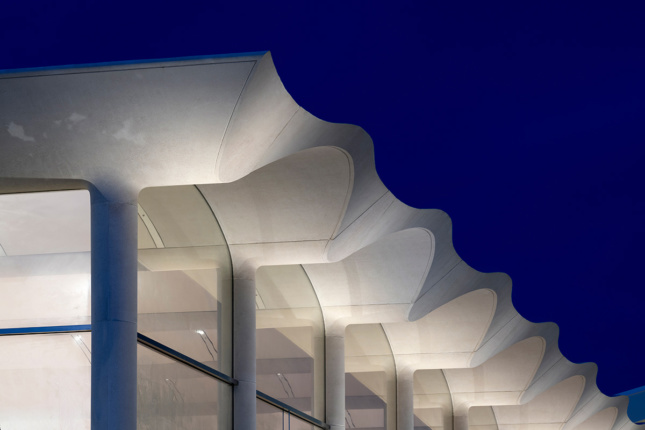 Close up night shot of white concrete arches on roof