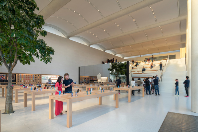 Interior shot of Apple store with tree, wooden display tables, terraced seating
