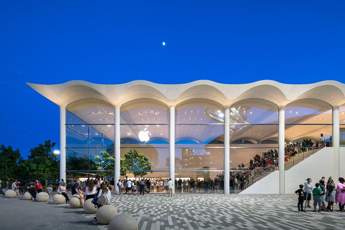 Twilight shot of glass-clad Apple store with undulating white roof situated next to mall plaza