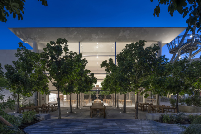 Twilight shot of courtyard with trees and wooden tables outside light-filled boxy building
