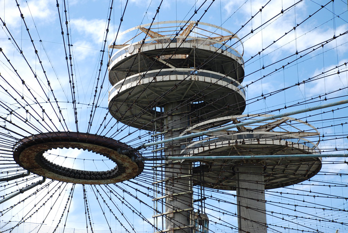 Close up image of concrete towers with observation platforms, seen through uncovered tent structure that makes up the New York State Pavilion