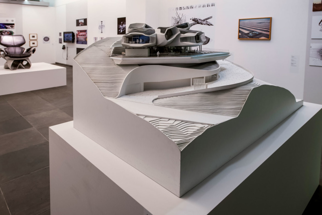 A photograph of an architectural model sitting on a podium in a white-walled gallery. Photographs, drawings, and other works of art are featured on the walls and on other podiums throughout the space.