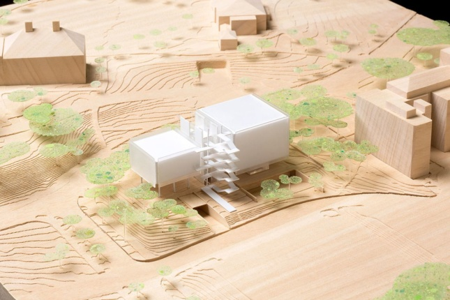 Model on a cardboard background of the new Agora Institute, with two square volumes