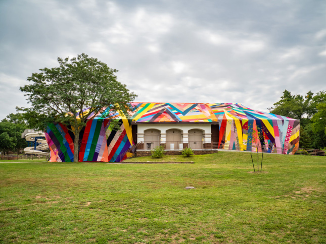 """A large fabric patchwork """"quilt"""" is draped over an entire building situated in a grassy expanse of a park in Grand Rapids."""
