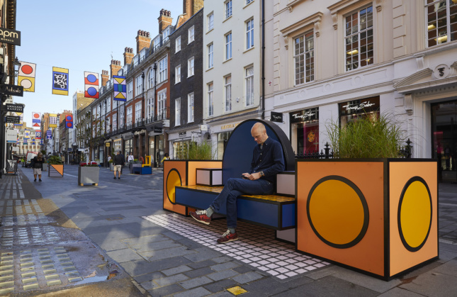 Photo of a man sitting on an orange bench at the London Design Festival