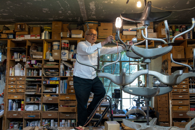 Older man stands on a ladder in a cluttered artist studio with a large metal sculpture sitting on a table.