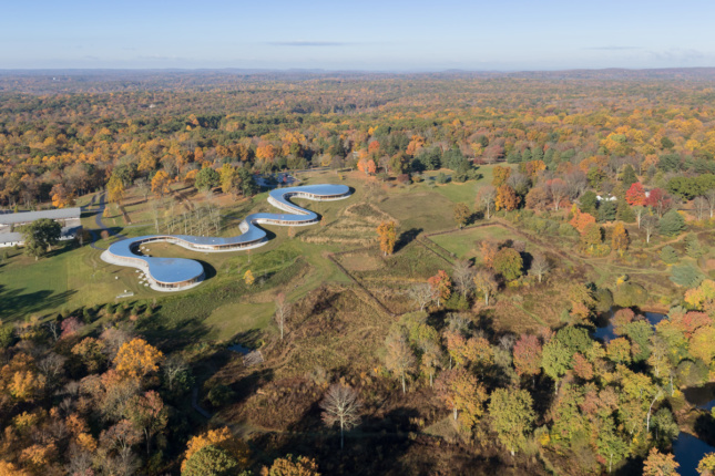 Aerial image during fall season of snake-like building in open field