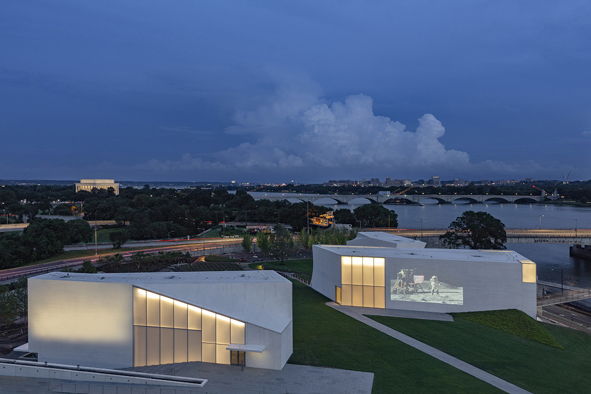 Aerial image of two angular white buildings on green campus lit at twilight by opaque glass windows, which forms The REACH